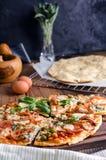 Corte en rebanadas deliciosas la pizza en la tabla de madera Imagenes de archivo