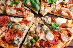 Corte en rebanadas deliciosas la pizza en la tabla de madera Fotografía de archivo