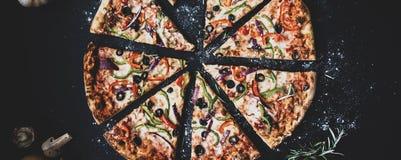 Corte fatias em deliciosas a pizza fresca com pepperoni e queijo da salsicha em um fundo escuro Vista superior com espaço da cópi imagem de stock royalty free