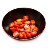 Corte fresco de los tomates de cereza por la mitad en la placa negra del cuenco aislada Imagen de archivo