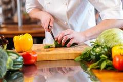 Corte fresco verde del pepino por las manos del cocinero profesional del cocinero Fotos de archivo