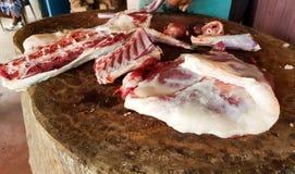 Corte gordo da carne vermelha manualmente em uma plataforma de madeira por um carniceiro com uma faca do cobre da carne imagem de stock