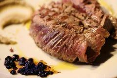 Corte la carne en un plato con las salsas y las pasas Foto de archivo