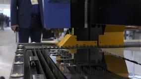 Corte la chapa Automatización del proceso Recorte de partes del metal La mano del ` s del hombre toma un detalle