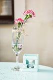 Corte la flor del geranio con la vela decorativa en la tabla Fotos de archivo libres de regalías