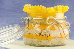 Corte la naranja con las gachas de avena en el pote, capa de jugo Imagen de archivo