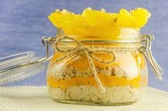 Corte la naranja con las gachas de avena en el pote, capa de jugo Imagen de archivo libre de regalías