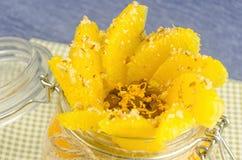Corte la naranja con las gachas de avena en el pote, capa de jugo Imágenes de archivo libres de regalías