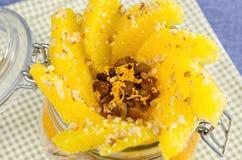Corte la naranja con las gachas de avena en el pote, capa de jugo Fotografía de archivo libre de regalías