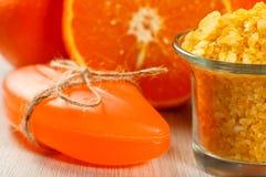 Corte la naranja, el jabón y el bol de vidrio con la sal de Yellow Sea Foto de archivo libre de regalías