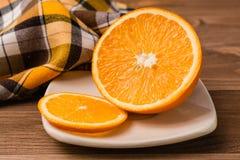 Corte la naranja en una placa en una tabla de madera Foto de archivo