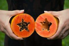 Corte la papaya en manos fotografía de archivo libre de regalías