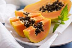 Corte la papaya en una tabla azul Fotos de archivo libres de regalías
