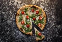 Corte la pizza de queso con la harina en la opinión superior del fondo concreto oscuro Foto de archivo libre de regalías