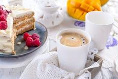 Corte la torta con la crema blanca, para la fruta del mango del desayuno A El fondo blanco, mantel con el cordón, una taza de caf fotografía de archivo