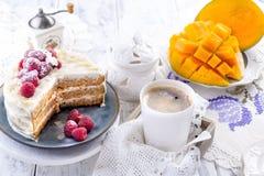 Corte la torta con la crema blanca, para la fruta del mango del desayuno A Fondo blanco, mantel con el cordón, una taza de negro  foto de archivo