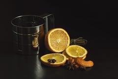 Corte a laranja, as varas de canela e um copo do metal em uma tabela de madeira escura Fotos de Stock Royalty Free