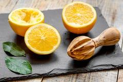 Corte laranjas ao meio e juicer no fundo de madeira Fotografia de Stock Royalty Free