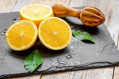 Corte laranjas ao meio e juicer no fundo de madeira Foto de Stock Royalty Free