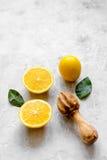 Corte laranjas e o juicer de madeira na opinião superior do fundo concreto Fotografia de Stock