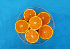 Corte laranjas na bacia de vidro no fundo azul Fotos de Stock