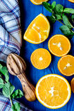 Corte las naranjas con las hojas y la toalla de menta en la opinión superior de la cocina azul fotos de archivo