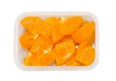 Corte las naranjas en pedazos en la caja plástica para adornan y comiendo encendido fotografía de archivo libre de regalías