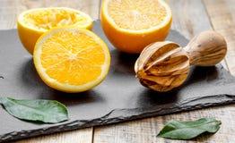Corte las naranjas por la mitad y el juicer en fondo de madera Fotografía de archivo