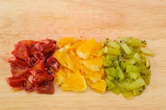 Corte las rebanadas de primer rojo y anaranjado de la naranja y del kiwi en tabla de cortar Fotografía de archivo