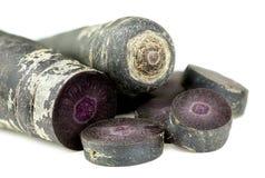 Corte las zanahorias púrpuras aisladas en la textura blanca del fondo Fotos de archivo libres de regalías