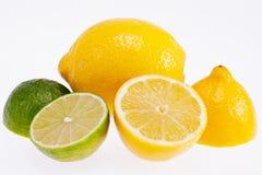 corte limões amarelos e os cais verdes isolados no fundo branco foto de stock royalty free