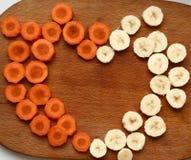 Corte los círculos de la zanahoria y del plátano que forman el corazón Imágenes de archivo libres de regalías