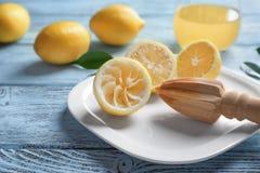 Corte los limones y el exprimidor de madera de la fruta cítrica Imágenes de archivo libres de regalías