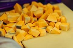 Corte los pedazos de la calabaza en el tablero plástico amarillo fotos de archivo