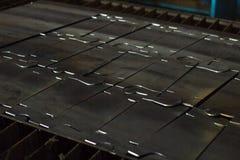 Corte los pedazos de piezas de metal en la chapa usando el corte moderno del plasma, para corte de metales imagen de archivo libre de regalías
