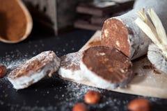 Corte los pedazos de salami del chocolate con las avellanas Fotos de archivo
