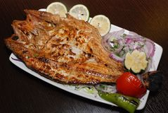 Corte los pescados con la ensalada, rebanadas de la cal, anillos de cebolla frescos en la placa blanca fotografía de archivo