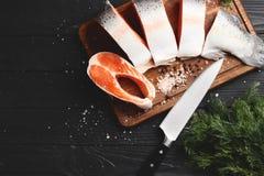 Corte los salmones frescos en una tabla de madera foto de archivo