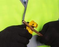 Corte mestre uma tubulação de cobre com um cortador de tubulação Fotos de Stock Royalty Free