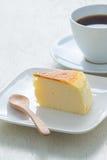 Corte o bolo de queijo com café quente na placa de madeira branca Fotografia de Stock Royalty Free