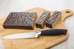 Corte o bolo e a faca do waffle do chocolate na placa de corte Fotografia de Stock