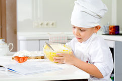 Corte o cozinheiro chefe pequeno que prova sua mistura da massa Imagem de Stock