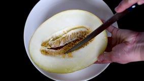 Corte o melão amarelo em uma placa lisa branca com uma faca filme