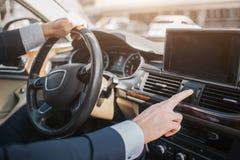 Corte a opinião o homem que senta-se no carro luxuoso Guarda uma mão no volante Uma outra mão toca em indicadores no painel fotografia de stock royalty free