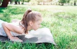 Corte a opinião uma menina pequena que encontra-se no carimate Está estando na posição da prancha A menina é concentrada uma vist Foto de Stock Royalty Free