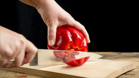 Corte a paprika vermelha na placa de corte de madeira video estoque