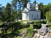 Corte pequena branca de Vlaska da igreja Aka vista atrás sobre de um promontório na natureza Capital ex de Cetinje de Montenegro fotos de stock royalty free
