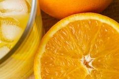 Corte recentemente a laranja com vidro de cubos do suco e de gelo na madeira Fotografia de Stock Royalty Free