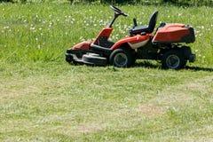 Corte recientemente la hierba por el cortacéspedes rojo imagen de archivo libre de regalías