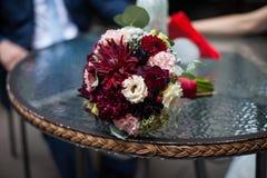 Corte recientemente las flores rojas y blancas en primer del ramo de la boda encendido Fotos de archivo